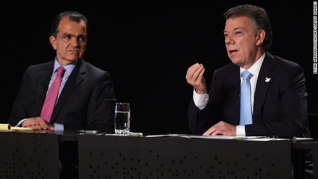 Colombia's President and presidential candidate, Juan Manuel Santos (R), speaks next to Colombian presidential candidate for the Democratic Center party, Oscar Ivan Zuluaga, during a TV debate in Bogota on May 22, 2014. Colombia's presidential elections will be held on May 25.