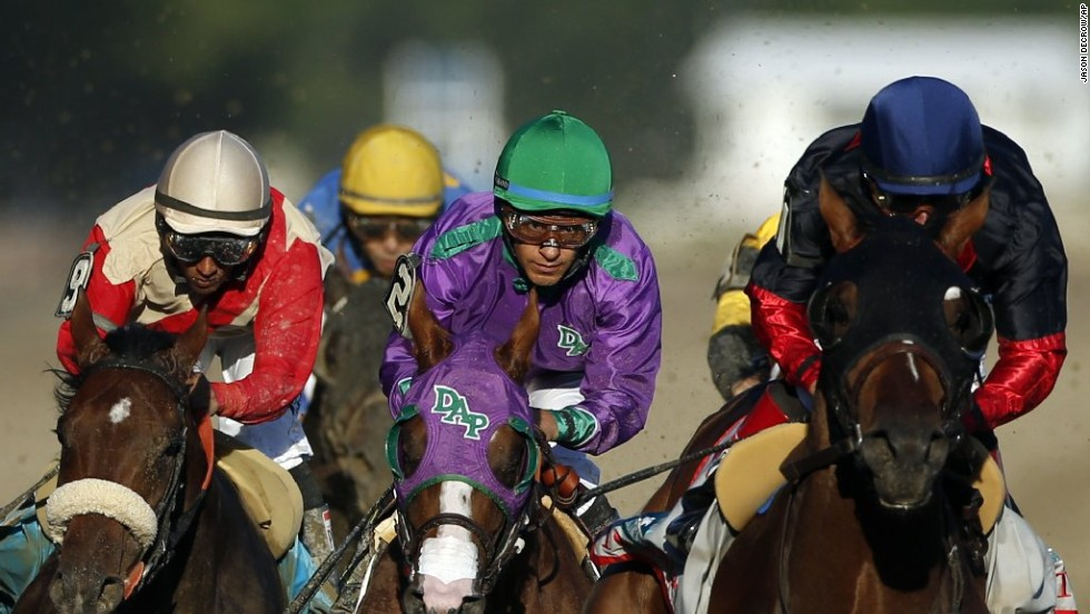 California Chrome, center, is flanked by Wicked Strong, left, and Tonalist, right, as they run down the backstretch.