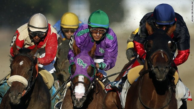 California Chrome, center, is flanked by Wicked Strong, left, and Tonalist, right, as they run down the backstretc.