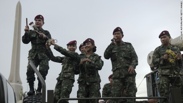 "To go with AFP Story 'Thailand-politics-army-propaganda',FOCUS by Amelie Bottollier-Depois In a picture taken on June 5, 2014 Thai soldiers sing as they stand on an army truck to entertain people at Victory monument in Bangkok. With free meals, music concerts and dancing soldiers, Thailand's junta is waging a propaganda offensive to encourage ""national happiness"" following a military coup that has severely restricted civil liberties. AFP PHOTO/"