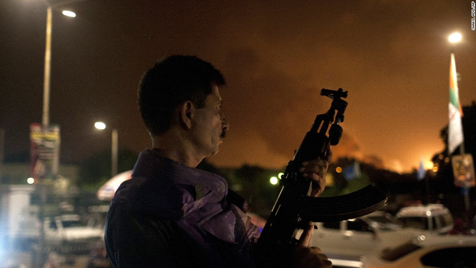 A Pakistani soldier holds his weapon ready at the airport Sunday, June 8. A building caught fire in the attack, but no planes were damaged, a military spokesman said.
