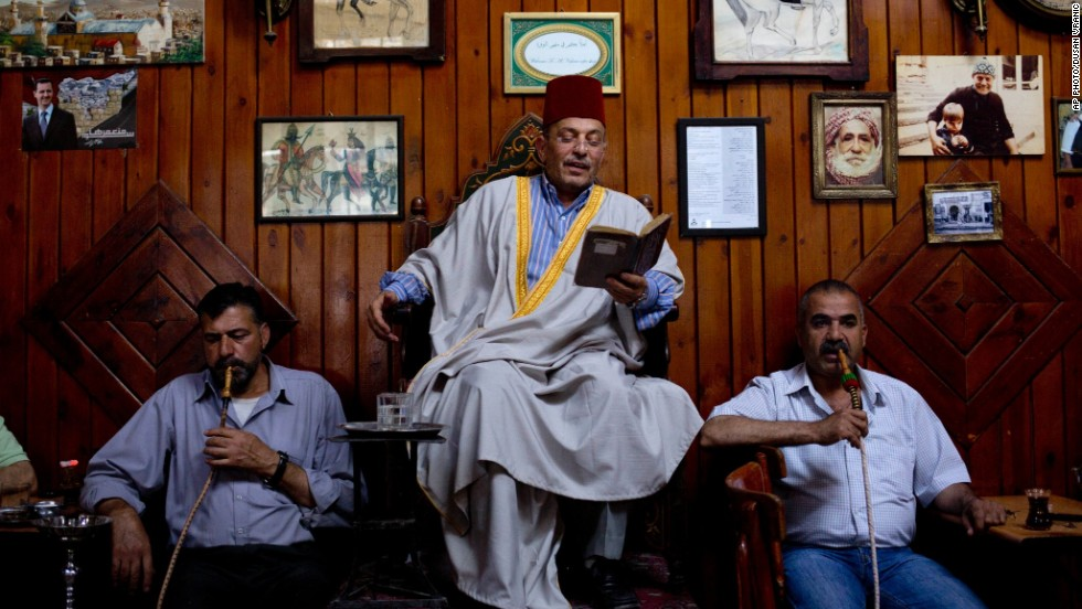 "JUNE 9 - DAMASCUS, SYRIA: Patrons listen to professional storyteller Ahmad Laham reading passages from a book in the al-Nofara café. The 3000-year-old eaterie in Damascus' stone-built Old City has always had ""hakawatis"" (storytellers) at evening gatherings."