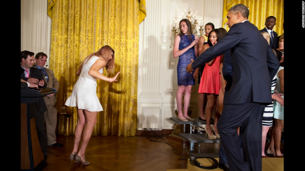 U.S. President Barack Obama reaches out to Stefanie Dolson after she slipped off the riser during a White House ceremony celebrating the University of Connecticut's basketball teams on Monday, June 9. Both the men's and women's teams at UConn won their respective NCAA championships.