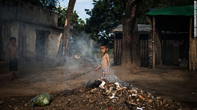 A boy pokes a trash fire in the Jan Mai Kawng IDP camp in Kachin State, Myanmar. About 600 people live in the camp.