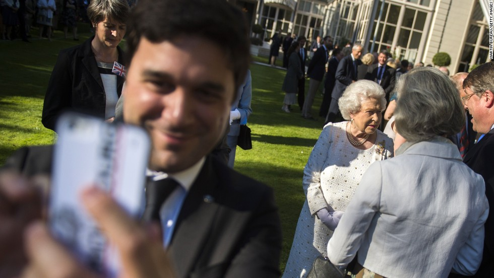 A man takes a selfie while, in the background, Queen Elizabeth II meets guests during a garden party at the British Embassy in Paris on Thursday, June 5.