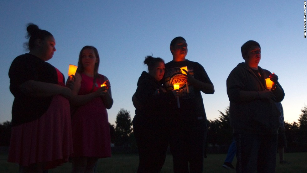 Friends, family and others hold candles for the victim of a school shooting at a vigil Tuesday, June 10 in Troutdale, Oregon, near Portland. A student shot and killed another student at Reynolds High School before apparently taking his own life, law enforcement sources said.