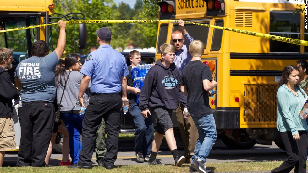 Buses arrive at a grocery store parking lot in Wood Village on June 10 to reunite students with their parents after the shooting.