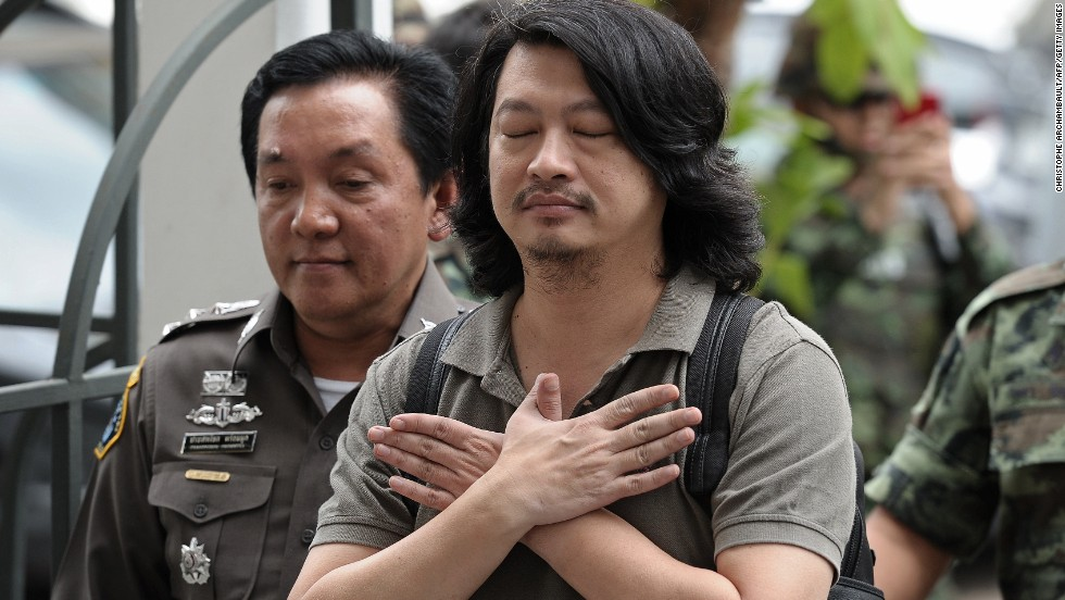 Thai anti-coup activist Sombat Boonngamanong, center, gestures as he arrives escorted by police and soldiers at a military court in Bangkok on Thursday, June 12. The prominent anti-coup figure faces up to 14 years in prison if convicted of incitement, computer crimes and ignoring a summons by the junta, police said. The Thai military carried out a coup May 22 after months of unrest had destabilized the country's elected government and caused outbursts of deadly violence in Bangkok.