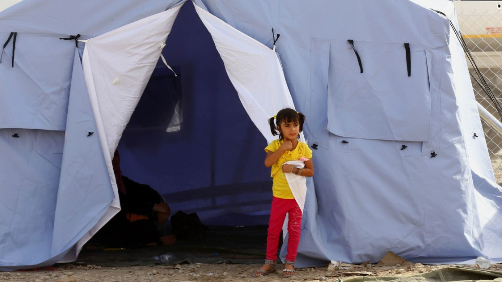 A girl from Mosul stands outside her family's tent at a refugee camp near Erbil on Wednesday, June 11.