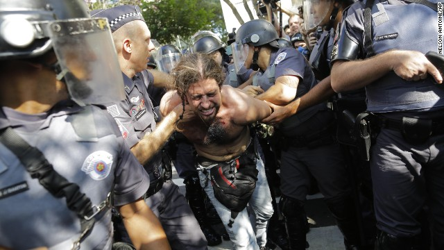 A protester is detained by police during a demonstration by people demanding better public services and against the money spent on the World Cup soccer tournament in Sao Paulo, Brazil, Thursday, June 12, 2014. Brazilian police clashed with anti-World Cup protesters trying to block part of the main highway leading to the stadium that hosts the opening match of the tournament. (AP Photo/Nelson Antoine)