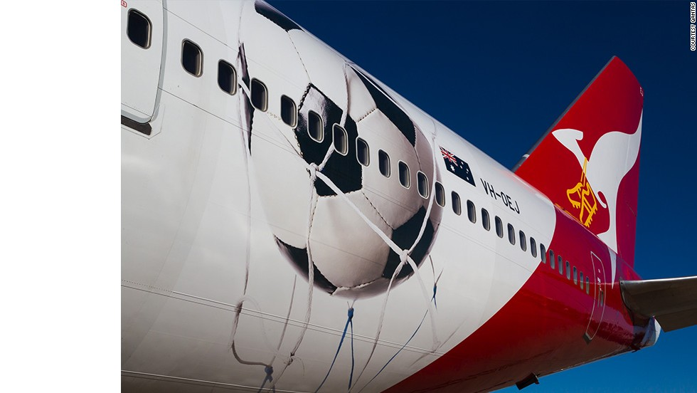 """Qantas is """"Proudly supporting the Socceroos"""" with a Boeing 747 decorated with a large football and a pair of golden boots strung around the airline mascot's neck. No jokes about choking, please."""