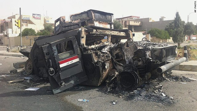 Iraqi army armored vehicle is seen burned on a street of the northern city of Mosul, Iraq, Thursday, June 12, 2014.