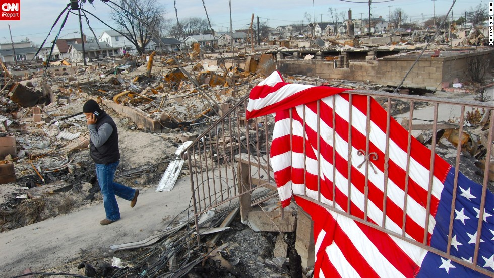 "An American flag drapes over the rails of a home that was ravaged by Superstorm Sandy in November 2012. <a href=""http://ireport.cnn.com/docs/DOC-881311"">Paul Lurrie</a> visited the Breezy Point community in New York soon after the storm came through. ""I felt a bit like I was walking on sacred ground. I sensed a solemn and somber atmosphere, but this is a close-knit community,"" he said."