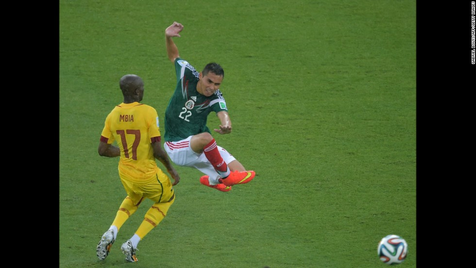 Mexico's Paul Aguilar jumps near Mbia.