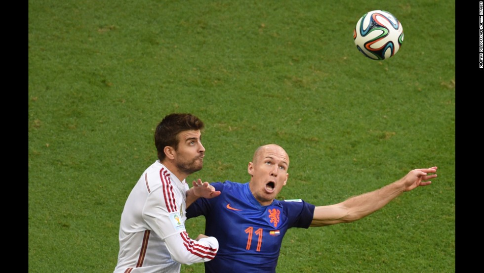Pique and Robben eye a ball in the air.