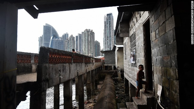 A boy walks into his house in Panama City's Boca La Caja neighborhood -- overlooked by new high-rise towers.