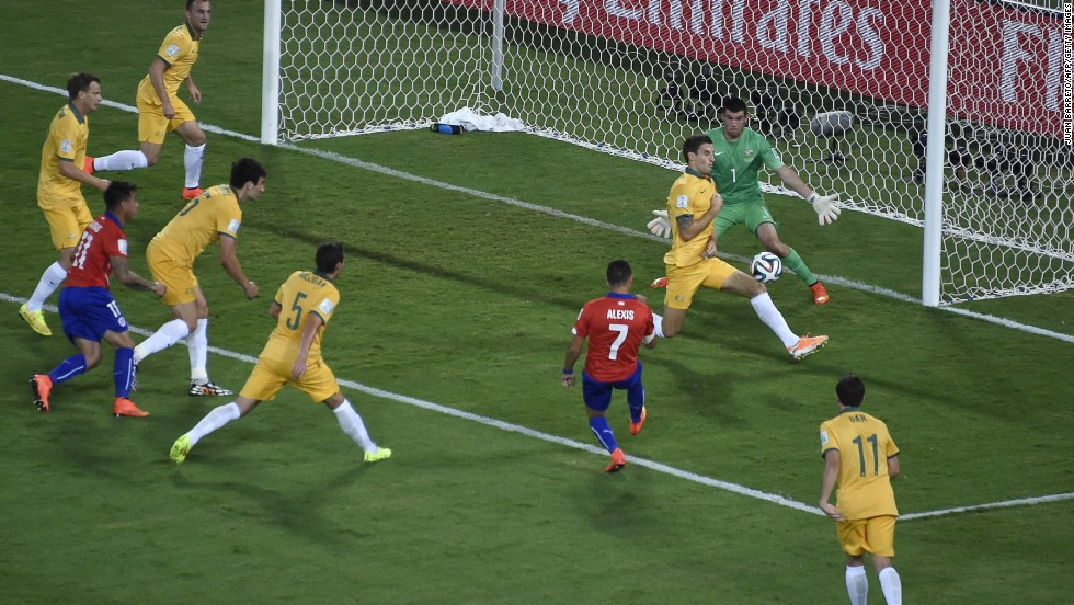 Chile forward Alexis Sanchez kicks the ball past two Australians to score the opening goal of the match.