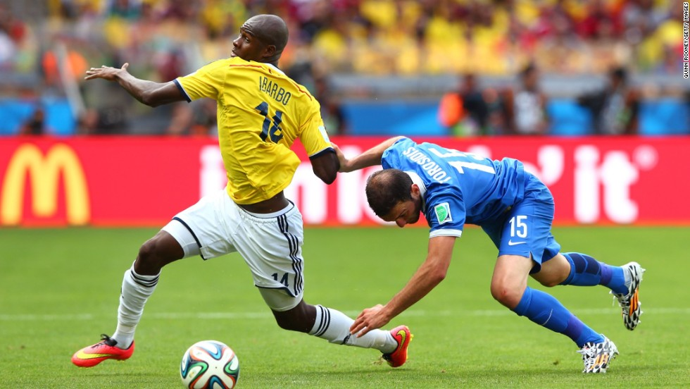 Victor Ibarbo of Colombia is challenged by Vasilis Torosidis of Greece.