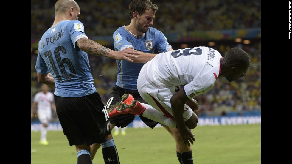 Uruguay defender Maximiliano Pereira, left, is sent off after this tackle on Costa Rica forward Joel Campbell during a World Cup match at Castelao in Fortaleza, Brazil.