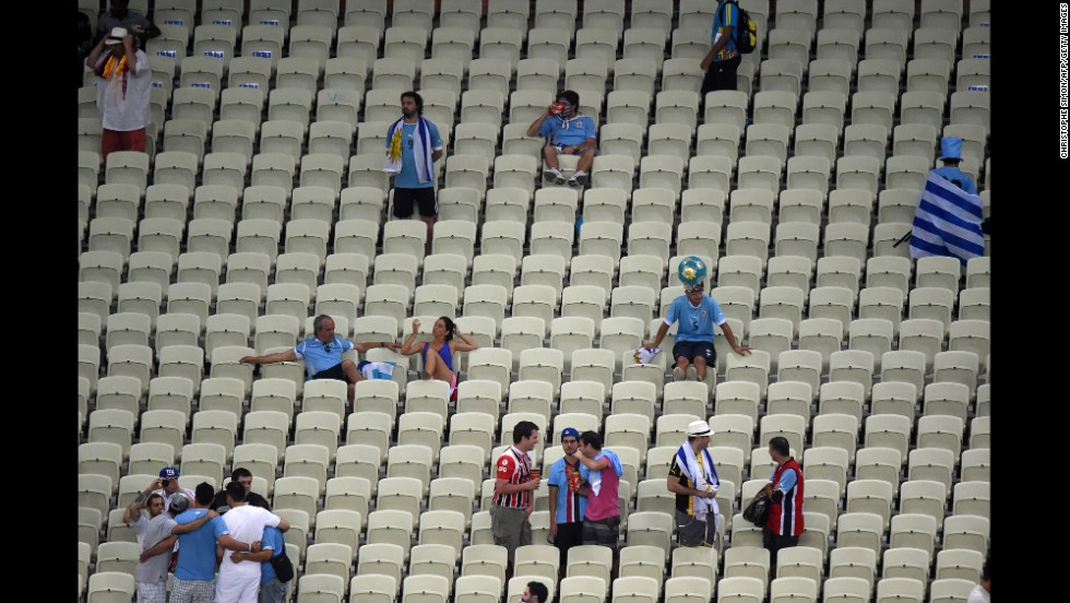 Uruguay fans, in blue, are pictured after their team's defeat to Costa Rica.