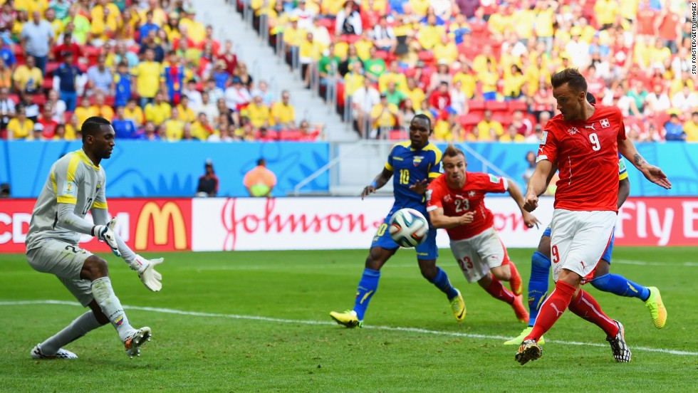 Substitute Haris Seferovic scores Switzerland's winning goal against Ecuador, beating goalkeeper Alexander Dominguez in the third minute of extra time to secure a 2-1 victory in the Group E opener June 15 in Brasilia, Brazil.