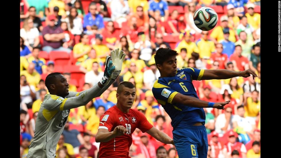 Switzerland midfielder Granit Xhaka, center, vies with Ecuador goalkeeper Alexander Dominguez, left,  and midfielder Christian Noboa.