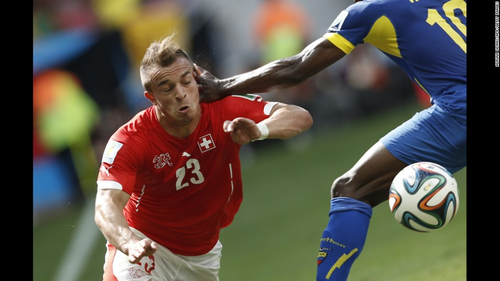 Switzerland midfielder Xherdan Shaqiri, left, goes to ground under a challenge from Ecuador's Walter Ayov.