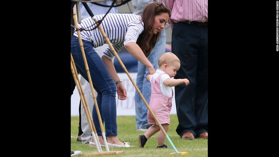 George takes his first steps in public as his mother holds his hand June 15 in Cirencester, England.
