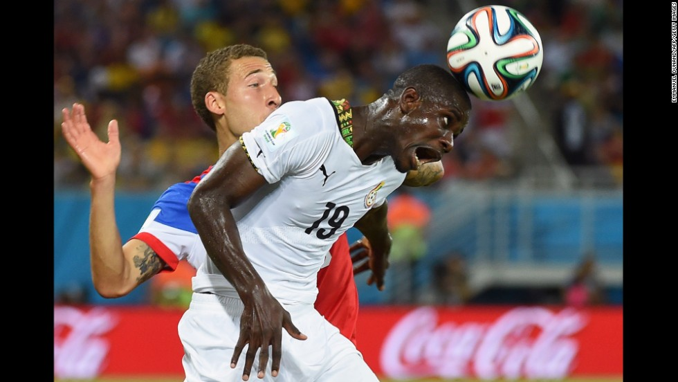Ghana defender Jonathan Mensah heads the ball in front of Johnson.