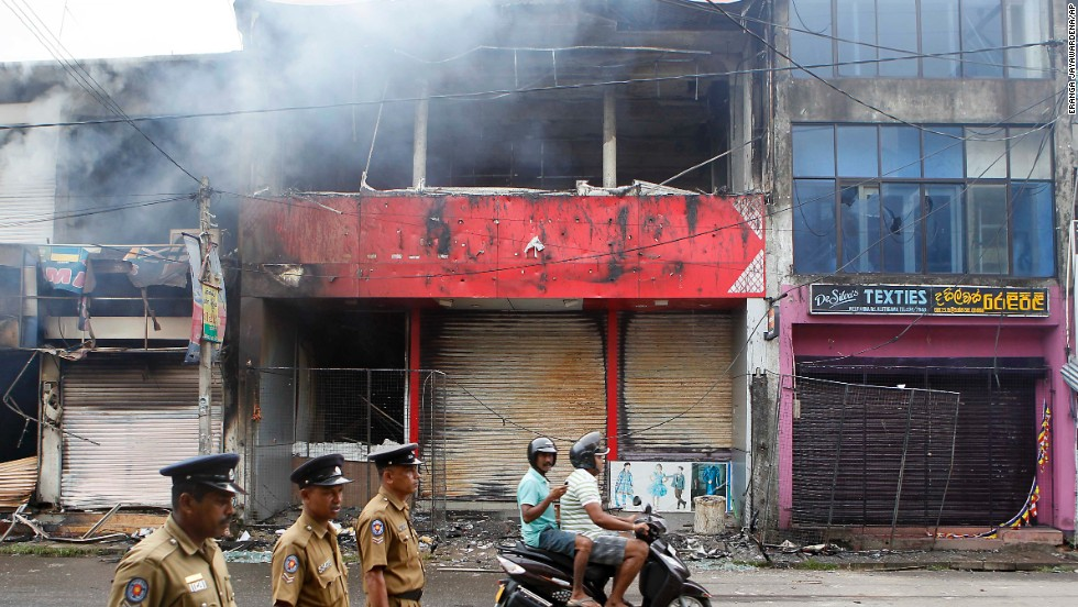 Police officers on a street in Aluthgama as shops burn. A curfew was put in place to prevent further violence.