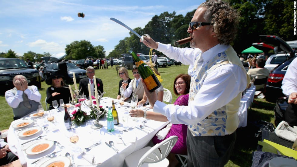 A man opens a bottle of champagne with a sword in front of fellow race goers as they enjoy the atmosphere during day one of Royal Ascot.  At last year's event racegoers enjoyed 51,000 bottles of champagne; 125,000 glasses of Pimms; 174,000 pints of beer; 5,000 kilos of salmon and 7000 crabs.