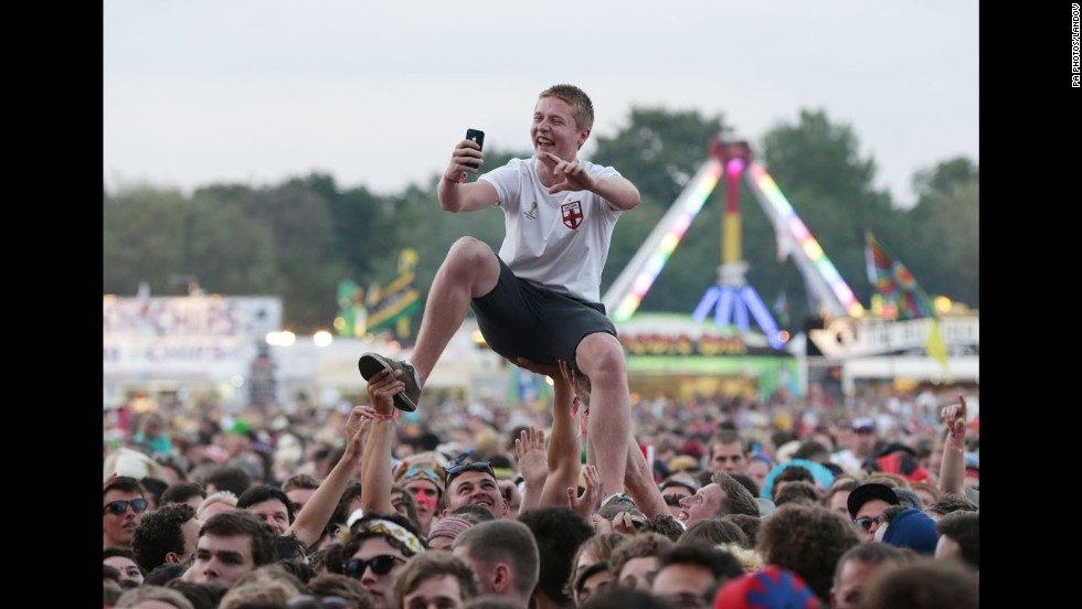 A festivalgoer takes a selfie above the crowd while The Specials play at the Isle of Wight Festival in Seaclose Park, England, on Saturday, June 14.