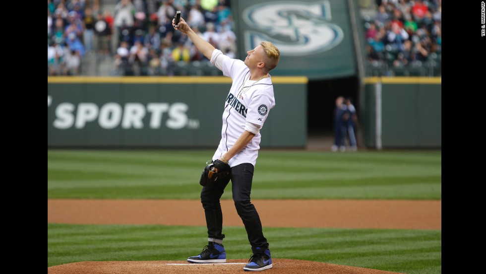 Rapper Macklemore takes a photo of himself on the mound at Seattle's Safeco Field before he threw out the first pitch before a Major League Baseball game between the Seattle Mariners and the New York Yankees on Thursday, June 12.