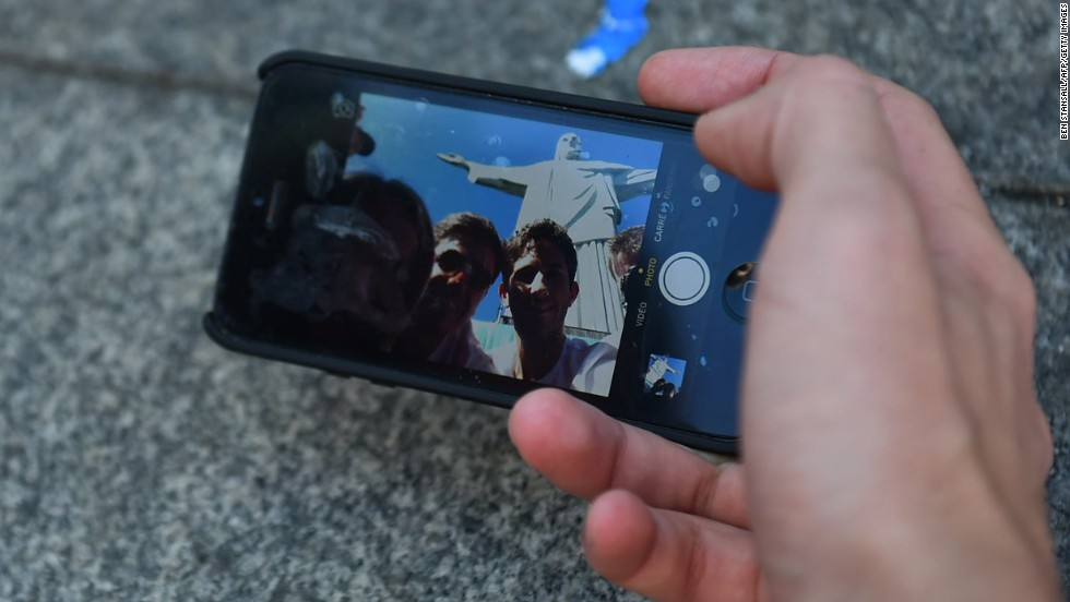 Tourists use a cell phone to photograph themselves with the Christ the Redeemer statue in Rio de Janeiro on Thursday, June 12.