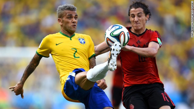 FORTALEZA, BRAZIL - JUNE 17:  Dani Alves of Brazil (L) controls the ball next to Andres Guardado of Mexico during the 2014 FIFA World Cup Brazil Group A match between Brazil and Mexico at Estadio Castelao on June 17, 2014 in Fortaleza, Brazil.  (Photo by Lars Baron/FIFA/Getty Images)