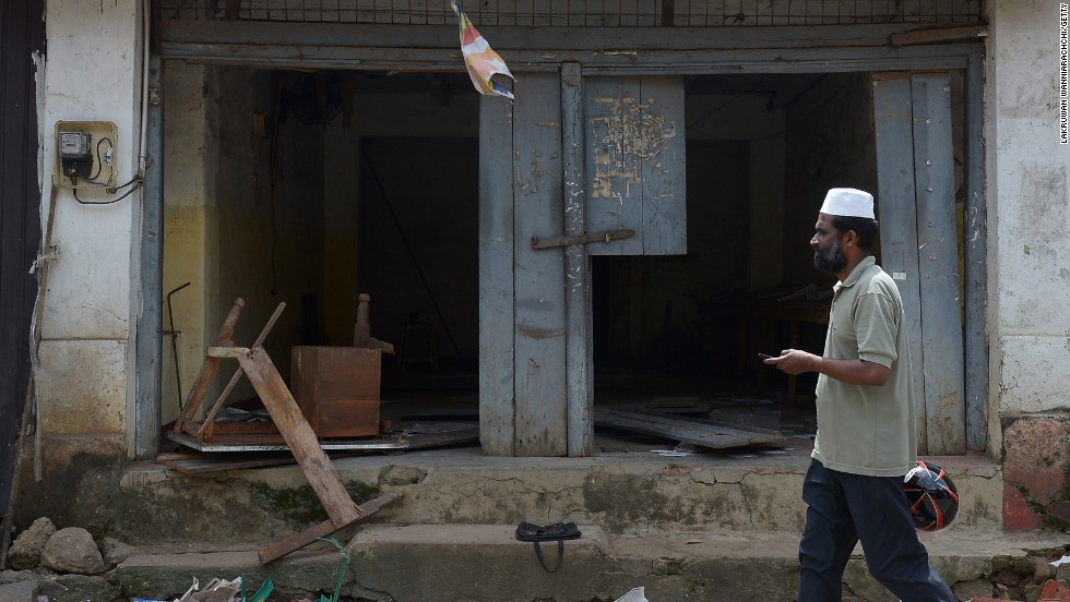 A Sri Lankan Muslim man walks past ransacked shops in Aluthgama.