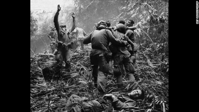 As fellow troopers aid wounded comrades, the first sergeant of A Company, 101st Airborne Division, guides a medevac helicopter through the jungle foliage to pick up casualties suffered during a five-day patrol near Hue, April 1968. (AP Photo/Art Greenspon)