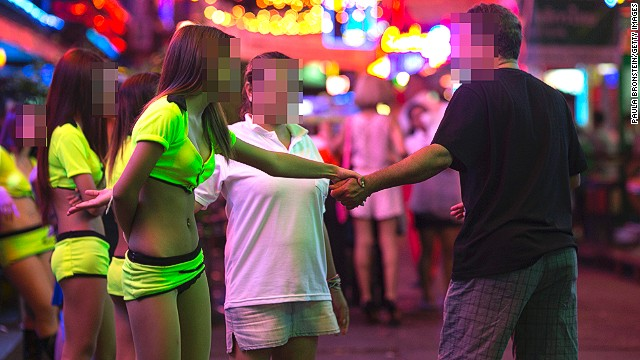 A woman waits for business outside a bar in Soi Cowboy.