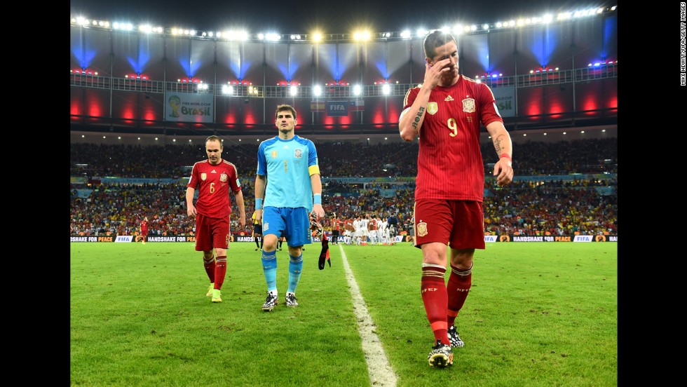 From left, Spanish players Andres Iniesta, Iker Casillas and Fernando Torres walk off the field after losing 2-0 to Chile. Four years after winning the World Cup, Spain is now the first team to be eliminated from the soccer tournament.