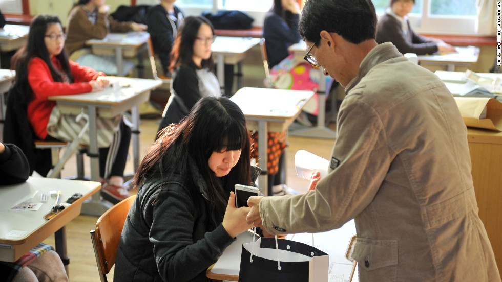 An examination invigilator collects mobile phones from South Korean students before they take the College Scholastic Ability Test, a standardized exam for college entrance, at a high school in Seoul on November 7, 2013.