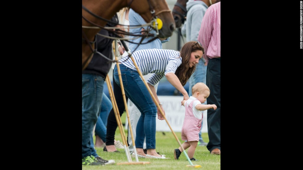 Britain's Prince George walks with his mother, the Duchess of Cambridge, while his father, Prince William, played in a charity polo match Sunday, June 15, in Cirencester, England.
