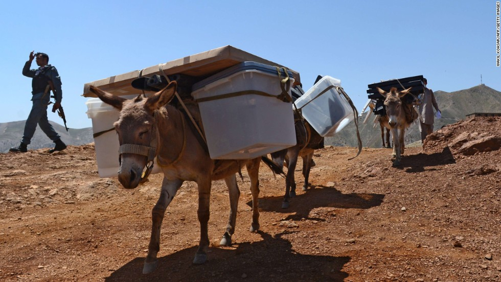 An Afghan policeman escorts villagers whose donkeys are carrying ballot boxes and other election materials in Afghanistan's Panjshir province on Friday, June 13. The next day, Afghans cast their votes in the presidential runoff between Abdullah Abdullah, the nation's former foreign minister, and Ashraf Ghani, a former finance minister. The results are scheduled to be released in July.