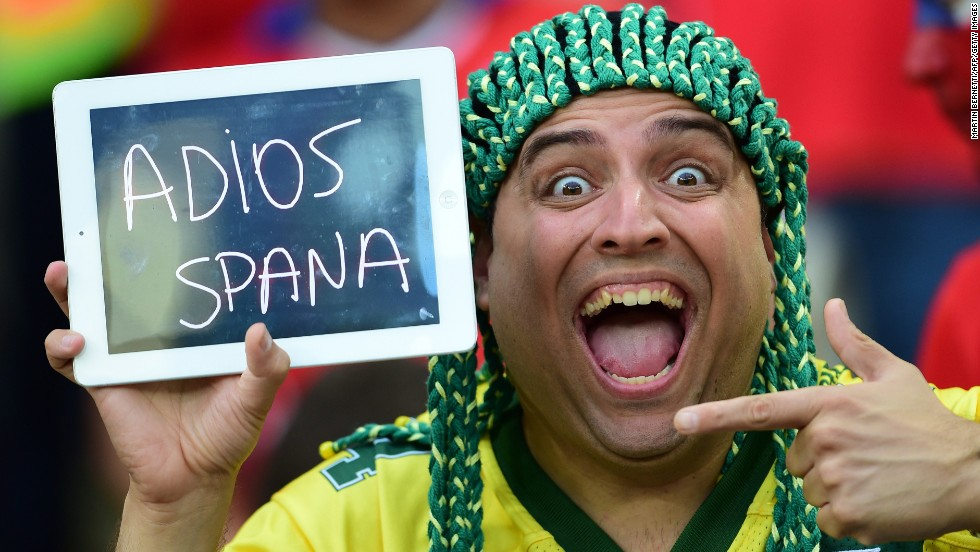 "A Chile soccer fan holds a sign saying ""Goodbye Spain"" after <a href=""http://www.cnn.com/2014/06/18/football/gallery/world-cup-0618/index.html"">Chile defeated Spain</a> in a World Cup match Wednesday, June 18, in Rio de Janeiro. Spain, who won the last World Cup, was one of the first teams to be eliminated in this year's competition."