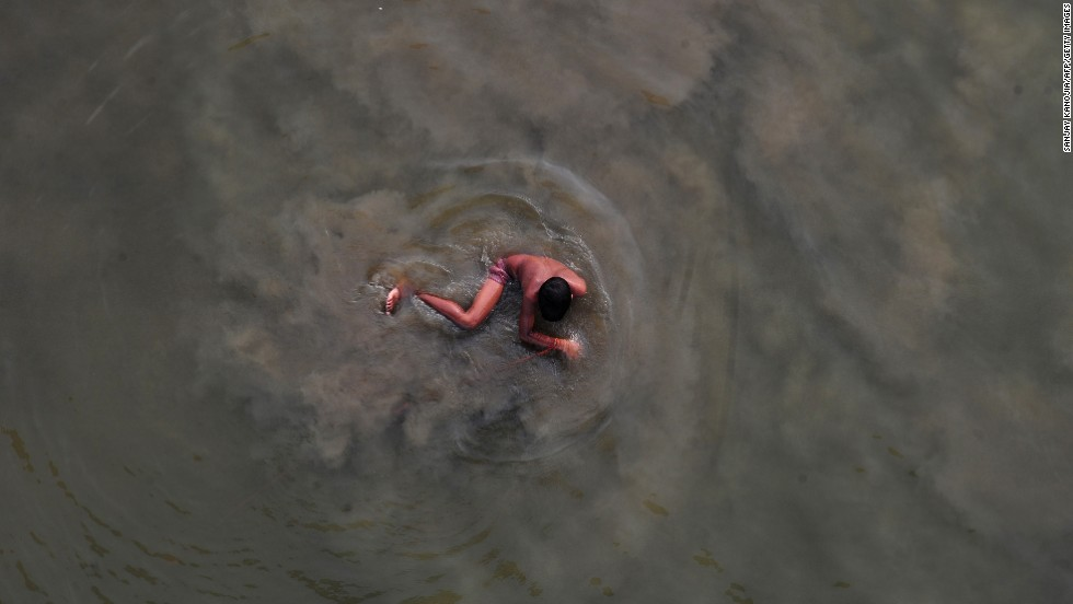 A boy cools off with a swim in the Yamuna river on a hot summer day in Allahabad, India, on Wednesday, June 18.