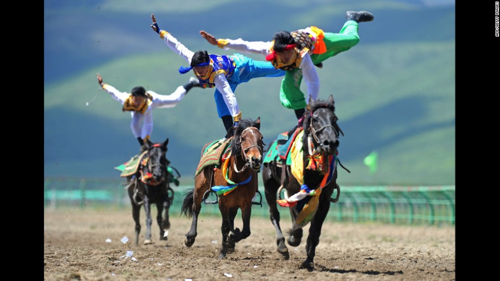 Riders wearing ethnic group costumes compete in a traditional horseback riding event Tuesday, June 17, in China's Sichuan province.