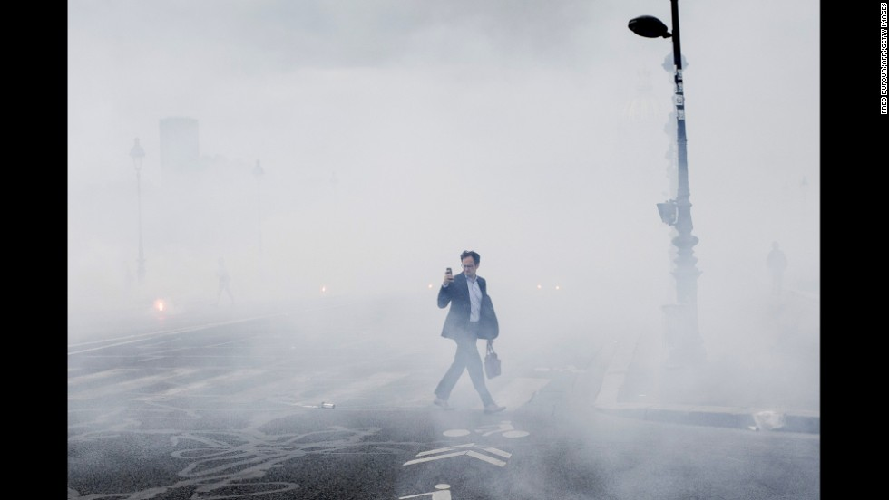 A man takes photos as he walks through smoke caused by flares Tuesday, June 17, in Paris. The flares were set during a demonstration staged by striking workers of SNCF, a state-run rail operator.