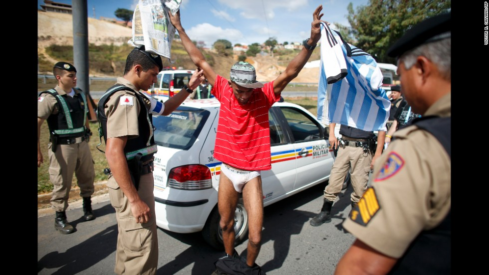 Denis Andre Oliveira, holding an Argentina soccer jersey, is searched by police in Vespasiano, Brazil, on Wednesday, June 18, after he was detained for entering the sports complex where Argentina's soccer team is training for the World Cup. Oliveira said he wanted to get an autograph from Argentina star Lionel Messi.