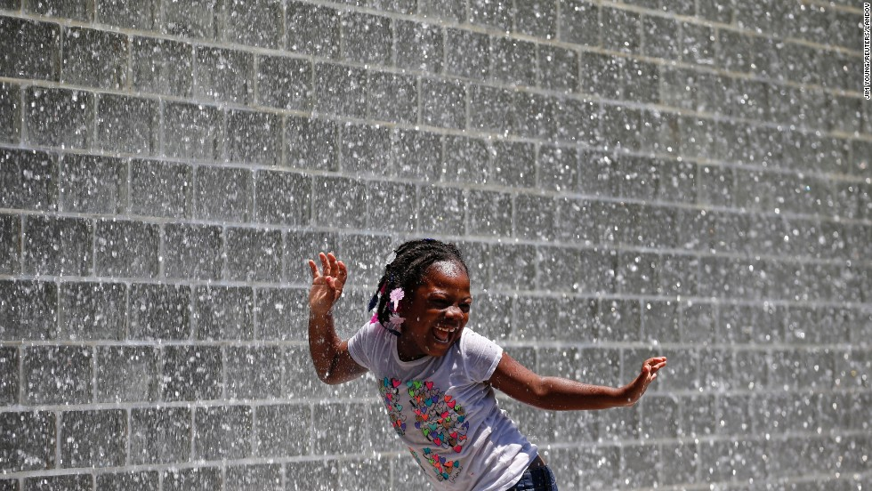 A girl dances under the waterfall of Chicago's Crown Fountain on Monday, June 16.