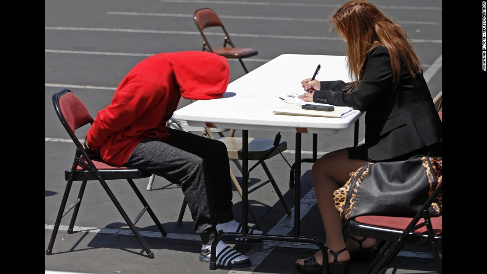 A suspected member of the Broadway Gangster Crips street gang puts his head on a table while he is interviewed by a law enforcement officer Tuesday, June 17, in Los Angeles. Seventy-two people linked to the gang were charged in a federal racketeering indictment for alleged murders, robberies and drug sales, according to police.