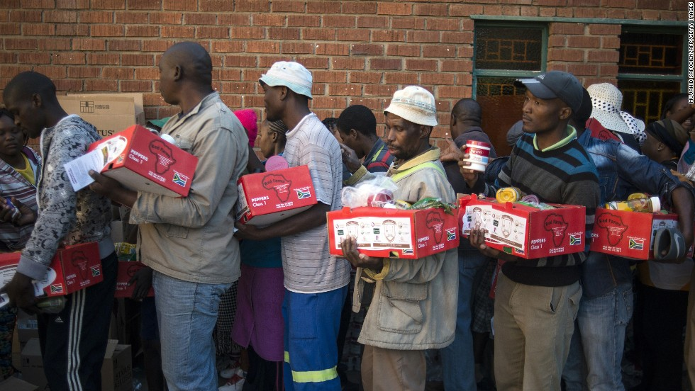 Striking miners from the platinum sector get in line to receive food parcels Friday, June 13, at a church in Marikana, South Africa. The strike has crippled the world's largest platinum producers.